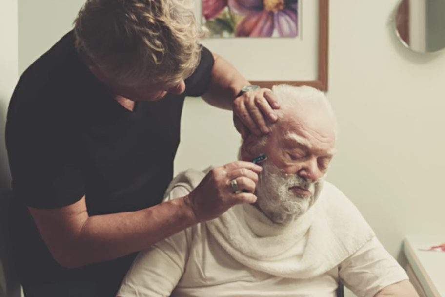 Man receiving assistance with shaving